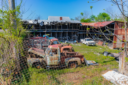 LIMESTONE, TN, USA-4/27/19:  A fenced yard containing junked antique trucks and cars, and a dilapidated building. Banque d'images - 122361108