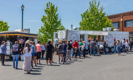 JOHNSON CITY, TN, USA-42719: People line up to make food purchases at vendors at a Saturday farmers market.