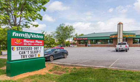 HICKORY, NC, USA-5319: A Family Video store, with street sign advertising CBD (cannabidiol) for sale.