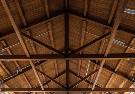 Underside of shed roof, showing trusses and plank roofing.