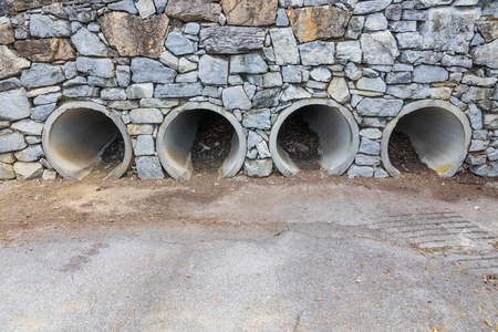 Four large pipes functioning as culverts through a rock wall, opening onto concrete parking lot.