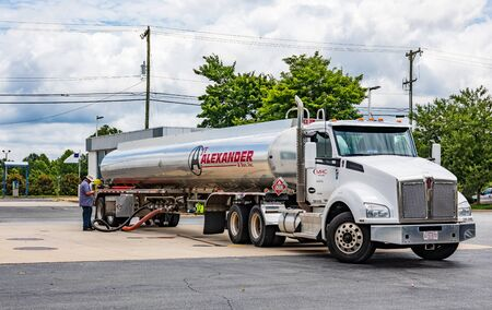 MOORESVILLE, NC, USA-JUNE 19, 2019:  An Alexander & Son tanker truck, filling a gas station tank, while driver stands by, looking at smart phone. Redakční