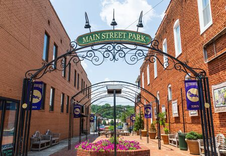 RUTHERFORD, NC, USA-27 JULY 19: A colorful urban park with flowers and greenery is bounded by two brick buildings. Redakční