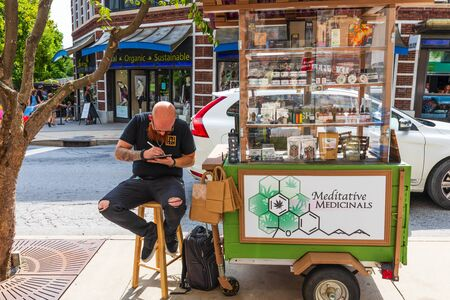 ASHEVILLE, NC, USA-27 JULY 2019: A tatooed man sitting on a stool in downtown Asheville sells Meditative Medicinals.
