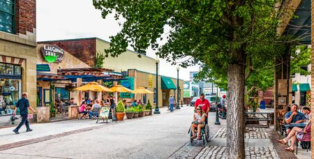 ASHEVILLE, NC, USA-27 JULY 2019: Wall Street in downtown is busy on a summer  Sunday, with small crowds at cafe tables, while a man pushes a young woman in a wheel chair. Redakční