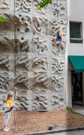 ASHEVILLE, NC, USA-27 JULY 2019: A small girl ascends a climbing wall while attached to a safety harness.  Another girl prepares to climb.