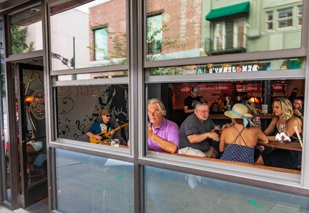 ASHEVILLE, NC, USA-27 JULY 2019:  The Asheville Club, a bar on Haywood Street, opens the doors and windows on a sunny, summer day.  A guitarist provides music for the crowd.