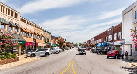 LINCOLNTON, NC, USA-9 AUGUST 2019: A view down main street on a sunny, summer day, with people and cars.