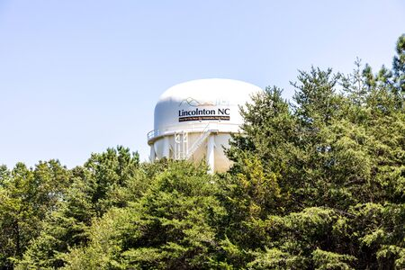 LINCOLNTON, NC, USA-9 AUGUST 2019:The city water storage tank, framed by evergreens and the blue sky.