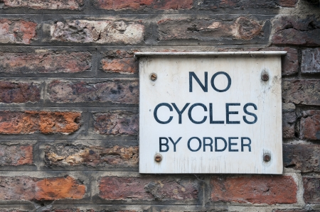 'cycles:  No cycles by order  sign on brick wall Stock Photo
