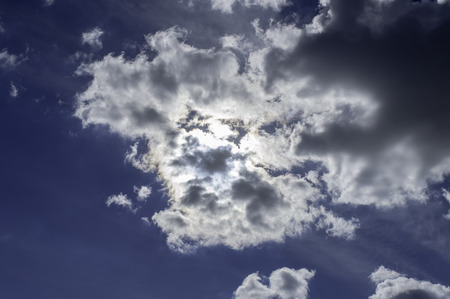 'hide out': The heavenly light of the sun cannot be extinguished as its brilliance brings out the beauty of the clouds attempting to hide it.