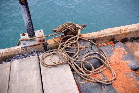 dark: Looses rope at harbor and dark blue sea