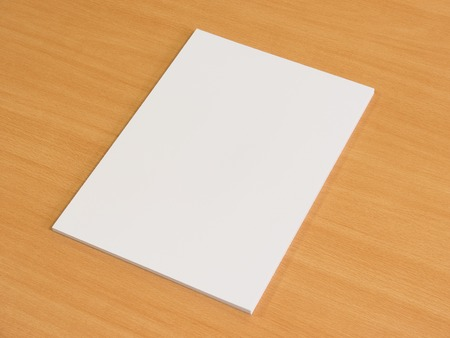 blank sign: White blank a pile of papers on wooden office table. Empty document.
