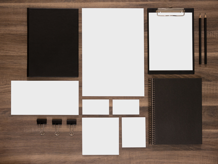 blank template: Branding mockup collection on brown wooden desk. Blank business cards with documents, envelopes and black notepads.
