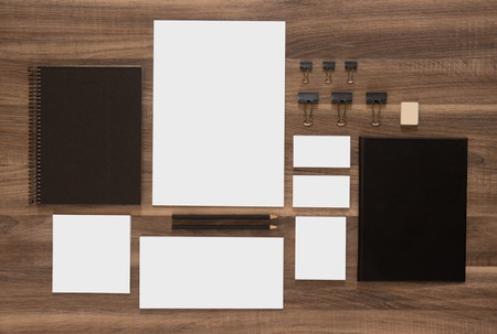 Mockup business brand template on wooden desk background. Set of stationery with black notepads. Фото со стока