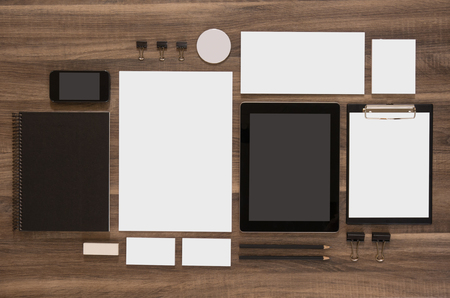 brands: Set of mock-up business brand template on wooden desk. Set of stationery with black notepads and tablet. Mobile phone.