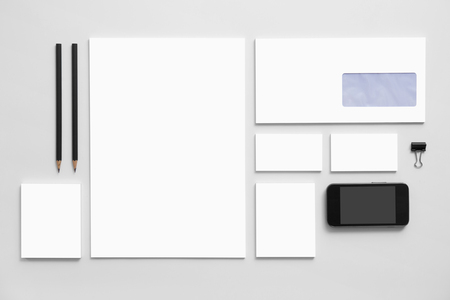 white paper: Mock-up business branding template on gray background. Set of stationery with a black mobile phone.