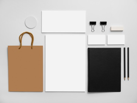 stationery background: Branding mockup with shopping bag. Set of stationery on gray background. Black notepad, blank business cards ant letterhead.