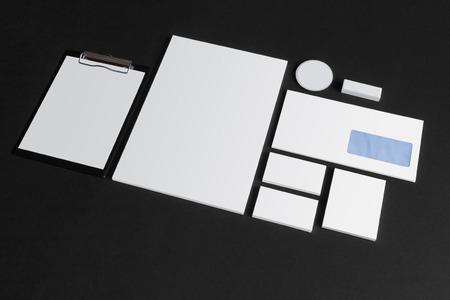 papeleria: En blanco de escritorio de marca situado en el fondo oscuro. Maqueta de presentación de diseño.
