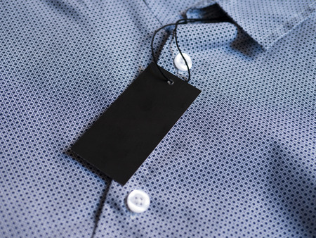 Label price tag mockup on blue shirt. Standard-Bild