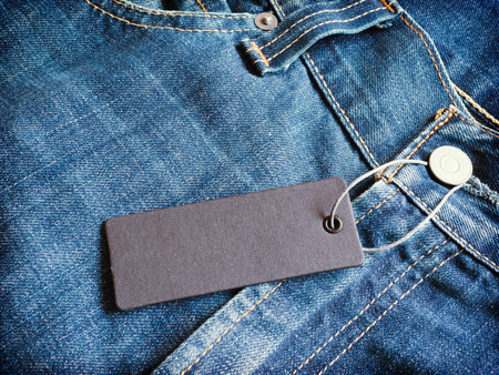 Label gray price tag mockup on blue jeans.