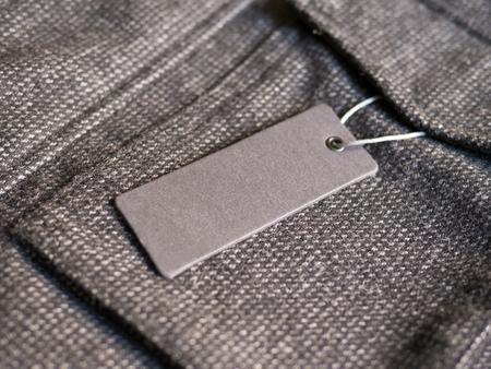 Blank label price tag mockup on brown coat. Standard-Bild