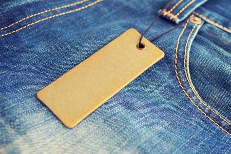 Blank label price tag mockup on blue jeans.
