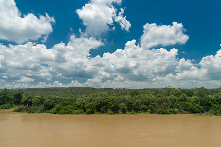 nature of clouds , blue sky, forest and river in a clear day