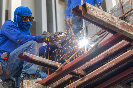 worker making sparks from welding steel in work place