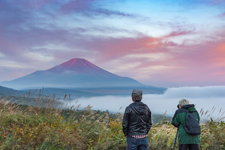 two men admired and shooting photo at mountain Fuji without snowcap in a summer morning with dramatic red clouds blue sky and mist below. Banco de Imagens