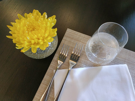 Top view of decorated table with crystal glasses, linen napkin, forks and yellow flower on luxurious tablecloths Banco de Imagens