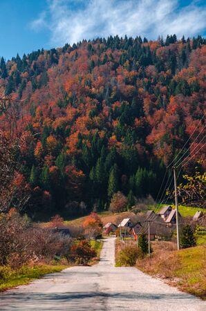Road going through a mountain village in an autumn scenery Фото со стока - 134825554