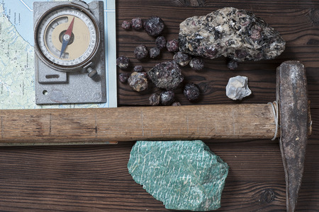 geological tools (map, geological compass, hammer) and minerals on a dark wooden table
