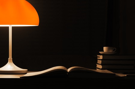 A table lamp with an orange lampshade lights up the books on the desk