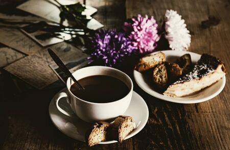 Cup of hot chocolate, cookies and flowers on an wooden table
