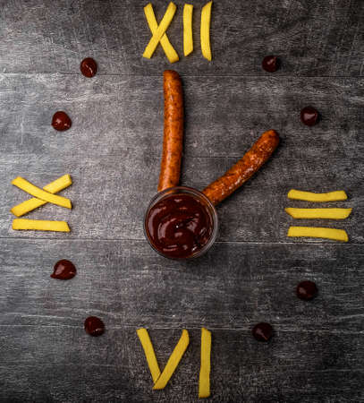 A clock made of fries, ketchup sausages. Lunch time. Creativity.