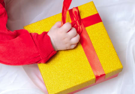Kid hands holding kraft paper gift box with present for Christmas, new year, valentine's day on white background, top view.