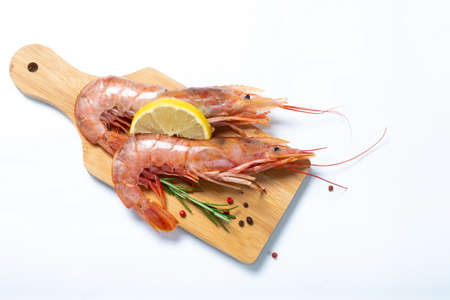 Two shrimps with lemon and rosemary on a cutting board. White background. View from above.