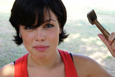 Angry lady ready to hit with a hammer photo