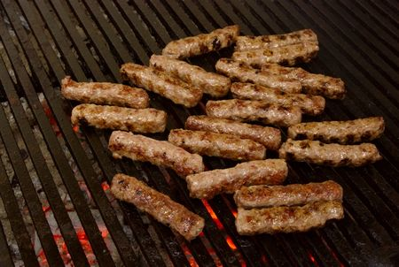 cevapi - a sort of rolled minced beef, pork and lamb meat preparing on grill similar to Turkish kebab. photo