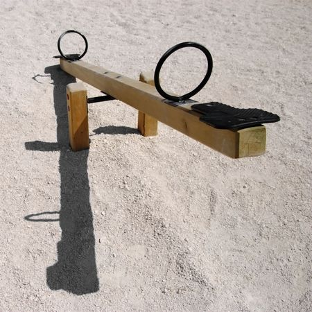 power saw: Empty wooden teeter-totter or seesaw with shadow - negative natality concept