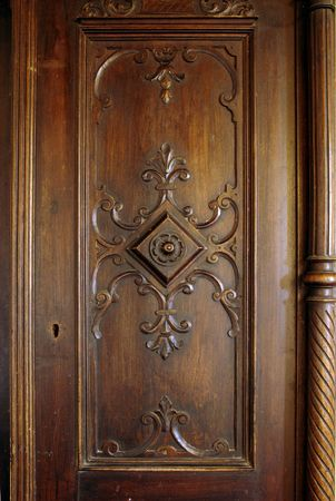 closet door: A picture of a wooden carved door of an antique closet