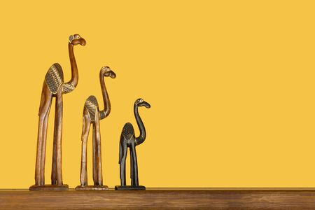 caravan of camels figures against yellow background with plenty of space for text photo