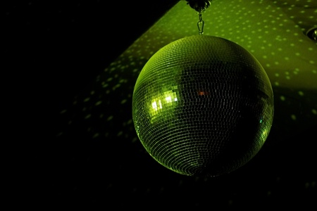 Disco ball in motion reflecting green light in night club with copy-space photo