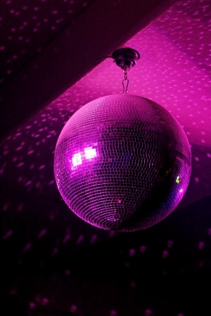 70s disco: Disco ball in motion reflecting pink light in night club with copy-space
