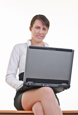 Office assistant in mini-skirt and white shirt sitting on top of office desk with laptop, eye contact photo
