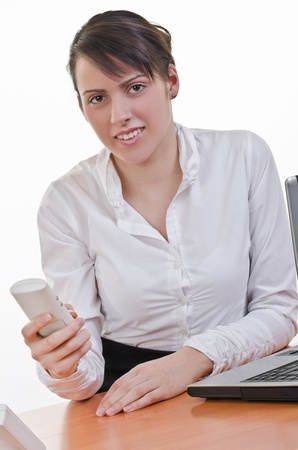 Portrait of a happy young woman holding phone in front of a laptop computer, high key, focus on eyes photo
