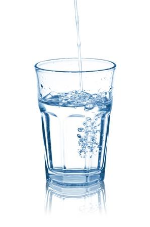 acqua vetro: versare l'acqua in vetro, isolato su bianco
