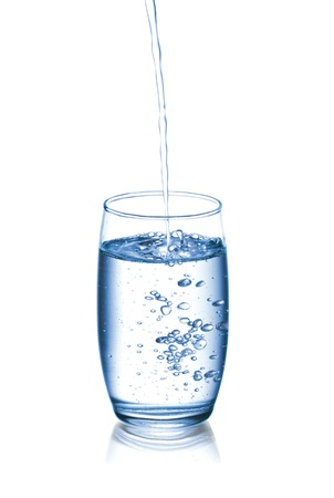 Photograph of pouring water into glass, isolated over white