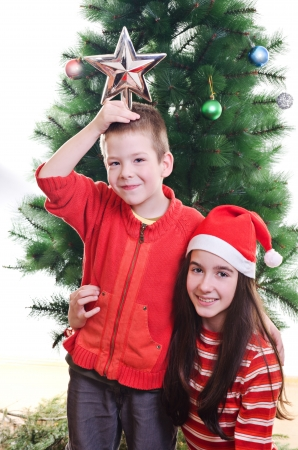 five to twelve: Young boy holding star on top of his head and sister wearing santa hat in front of christmas tree, portrait, looking at camera, vertical shot